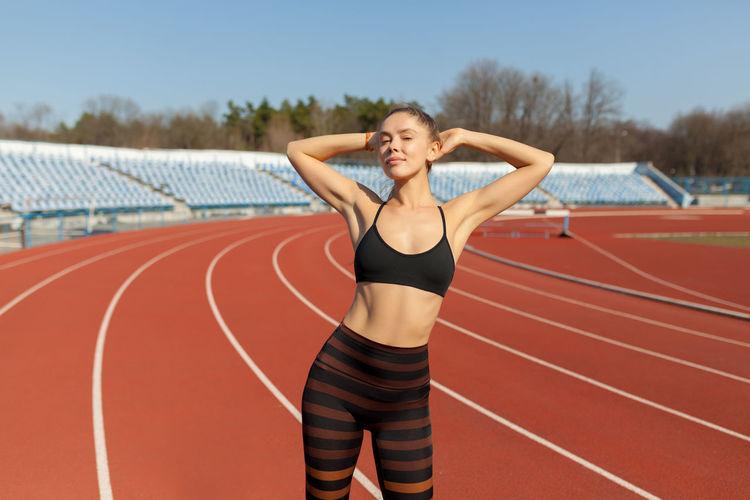 Woman exercising standing on stadium