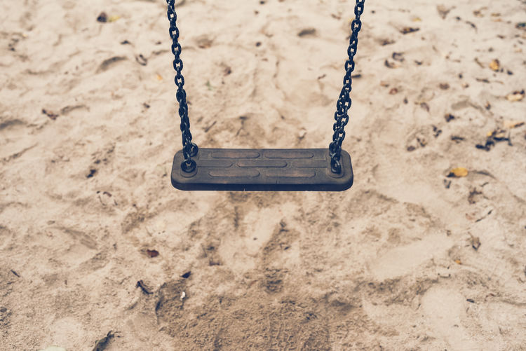 a empty swing with a sand ground Playground Swing Childhood Sand Chain Land Day Focus On Foreground Outdoor Play Equipment Hanging Outdoors Nature Empty Absence Metal Close-up High Angle View Innocence Loneliness Depression - Sadness