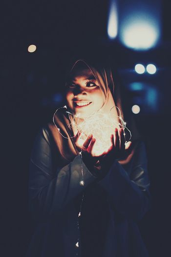 Happy young woman holding illuminated string lights at night
