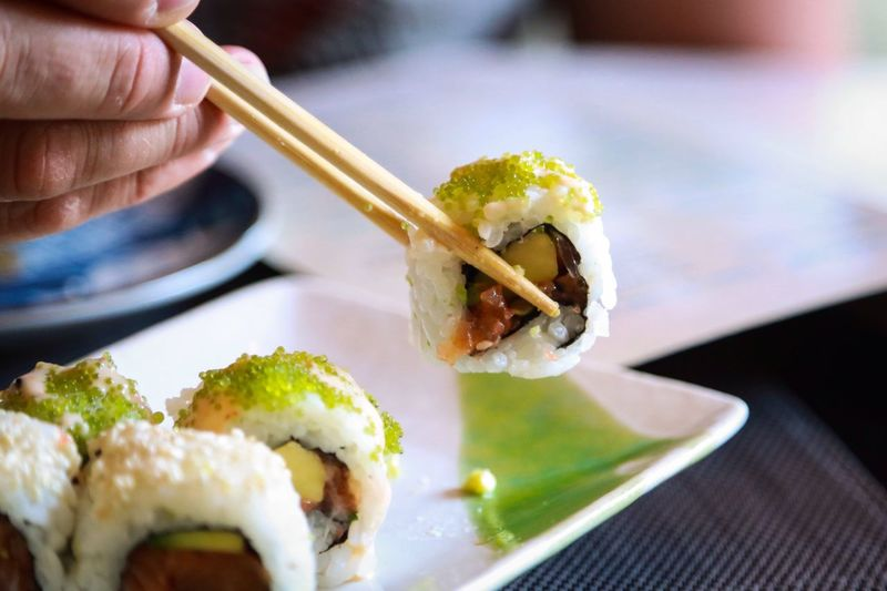 Cropped image of hand holding sushi with chopsticks on table