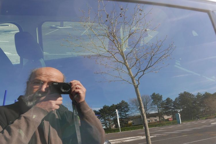 Reflection of man clicking selfie on car window