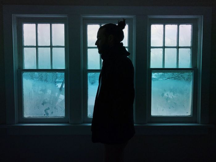 Side view of man standing by glass window during winter