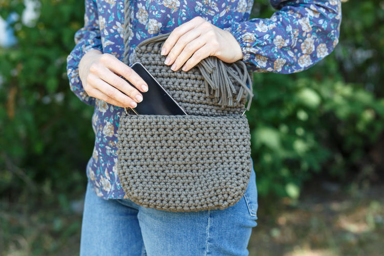 Midsection of woman removing mobile phone from purse