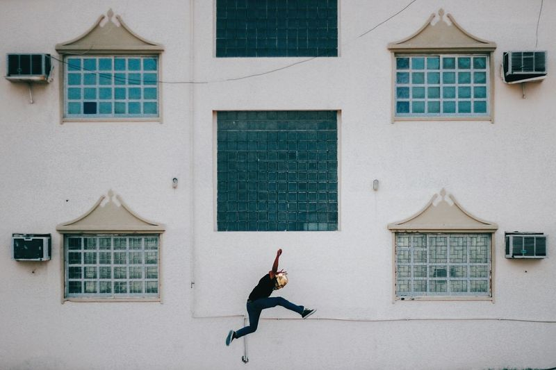 Man jumping against building
