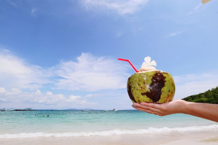 View of hand holding coconut drink on beach