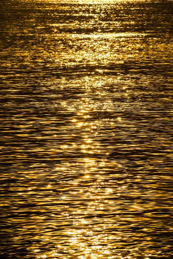 The color of the sunset was sprinkled on the river Reflection Sea Gold Colored Rippled Water Backgrounds Waterfront Sunset Nature Full Frame Dusk Tranquility Scenics Tranquil Scene Sunlight Outdoors No People Shiny Beauty In Nature Gold