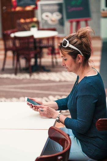 Woman using mobile phone while sitting at table in restaurant