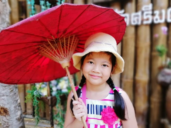 Portrait of a smiling girl holding hat