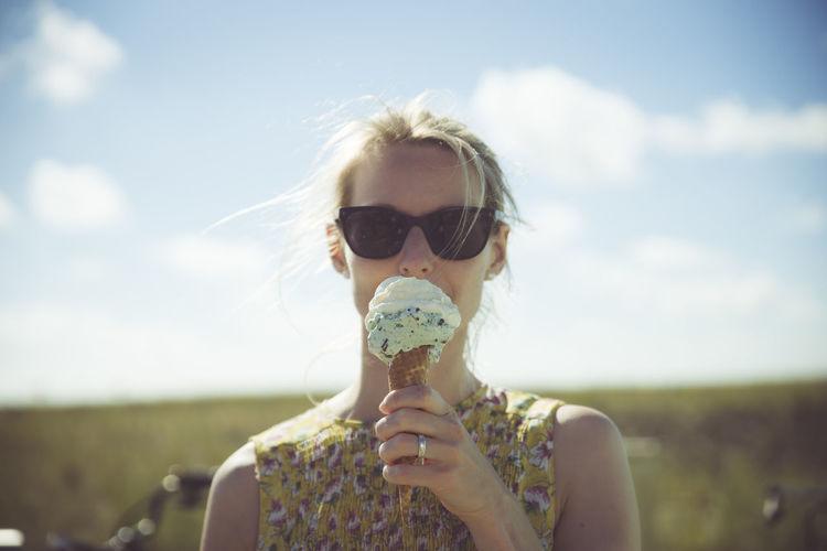Portrait of woman holding sunglasses against sky