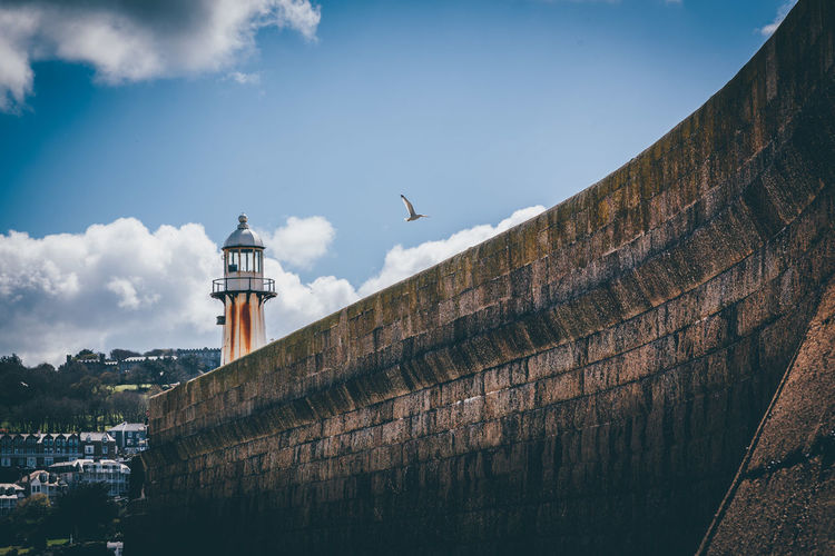 Low angle view of bird flying over wall by lighthouse against sky
