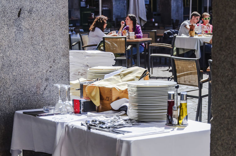 A table with plates and other objects for waiters near a terrazza in Plaza Mayor in Madrid (2012). Adult City City Life Day Eating Out Eating Outside Editorial  Madrid Outdoors Plaza Mayor Restaurant Streetphotography Table Terrazza Tourism Tradition Travel Travelling Women