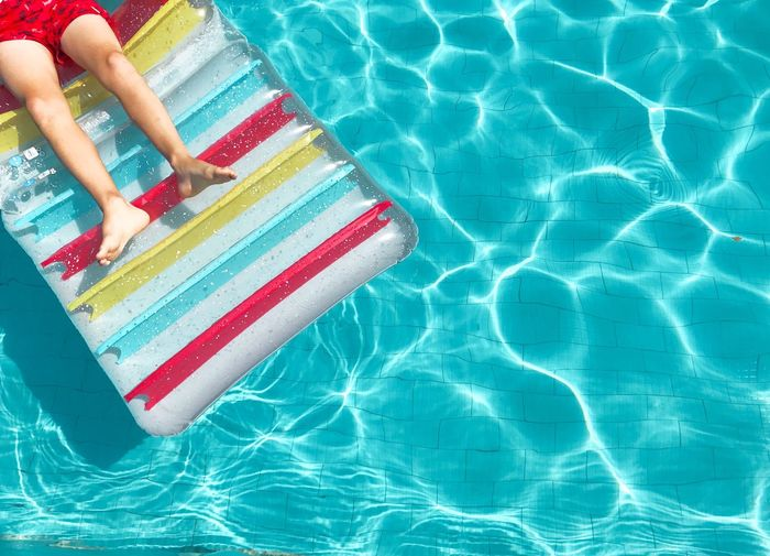 Low Section Of Boy Lying On Inflatable Raft In Swimming Pool During Summer