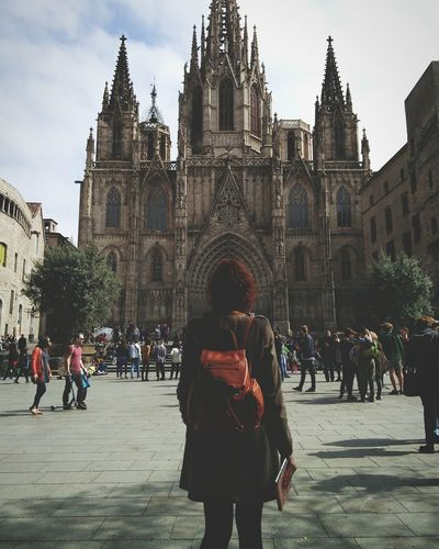 Rear View Of Woman Standing Against Barcelona Cathedral In City On Sunny Day