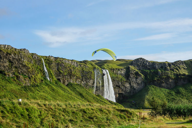 paragliders fly in the blue sky at Skógafoss Iceland with variation formation. Fly Iceland Paragliding Adventure Beauty In Nature Day Grass Green Color Mountain Nature Outdoors Paraglders Scenics Skogafoss Falls, Iceland Sky Tree Water Waterfall