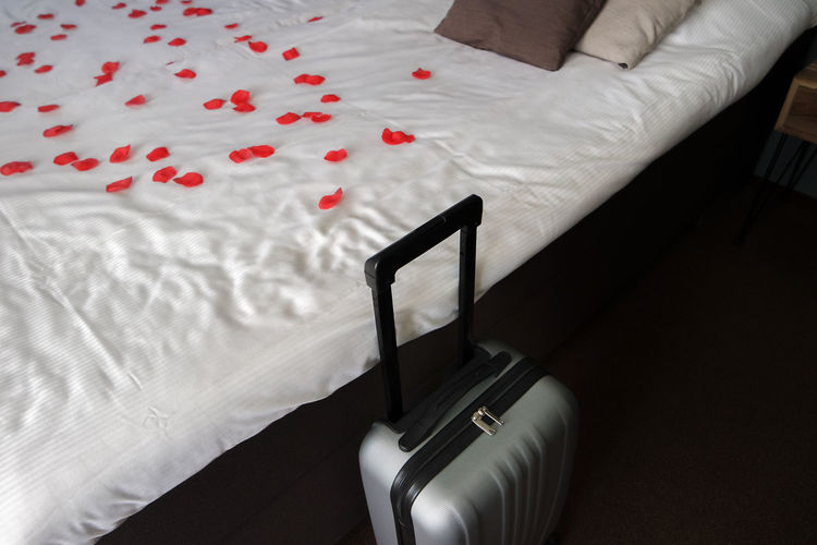 High Angle View Of Suitcase By Red Petals On Bed In Bedroom