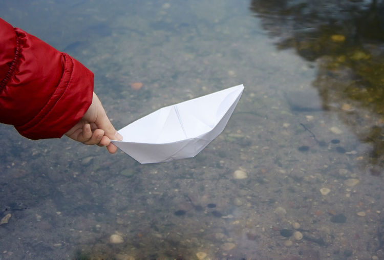 Close-up of woman holding paper boat over water