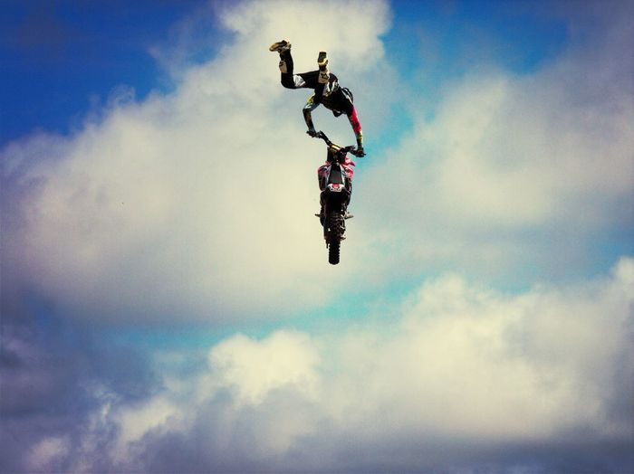 Low angle view of man in mid-air with motorcycle against cloudy sky