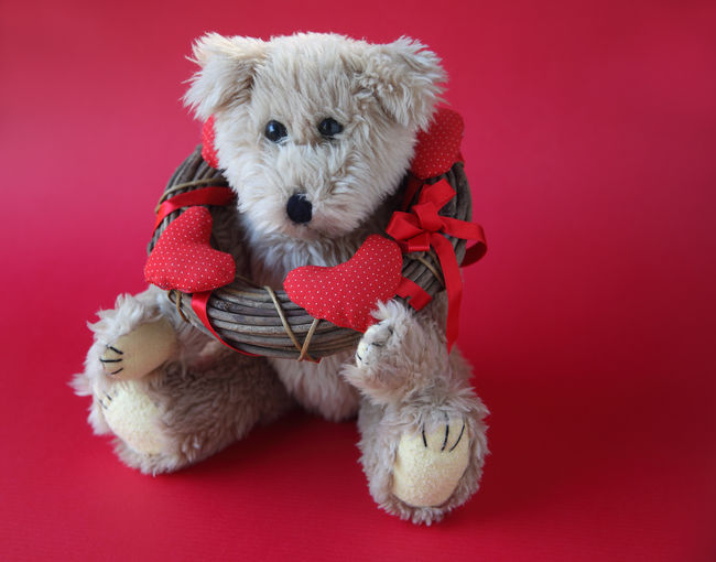 Close-Up Of Teddy Bear With Wreath On Red Background