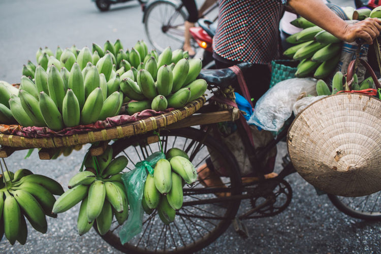 Low section of man carrying bananas on bicycle