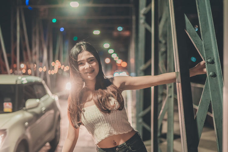 Portrait of smiling young woman standing on footbridge in city at night