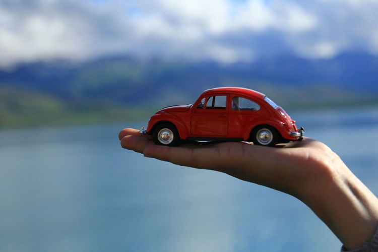 Cropped hand holding red toy car