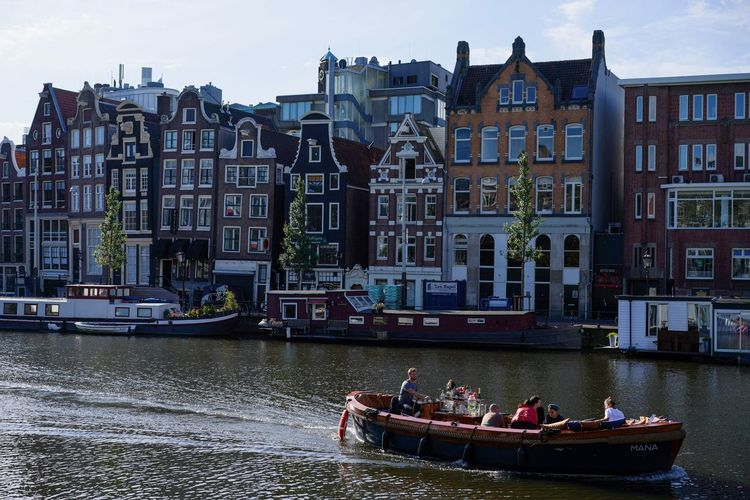 People on boat in river against buildings in city