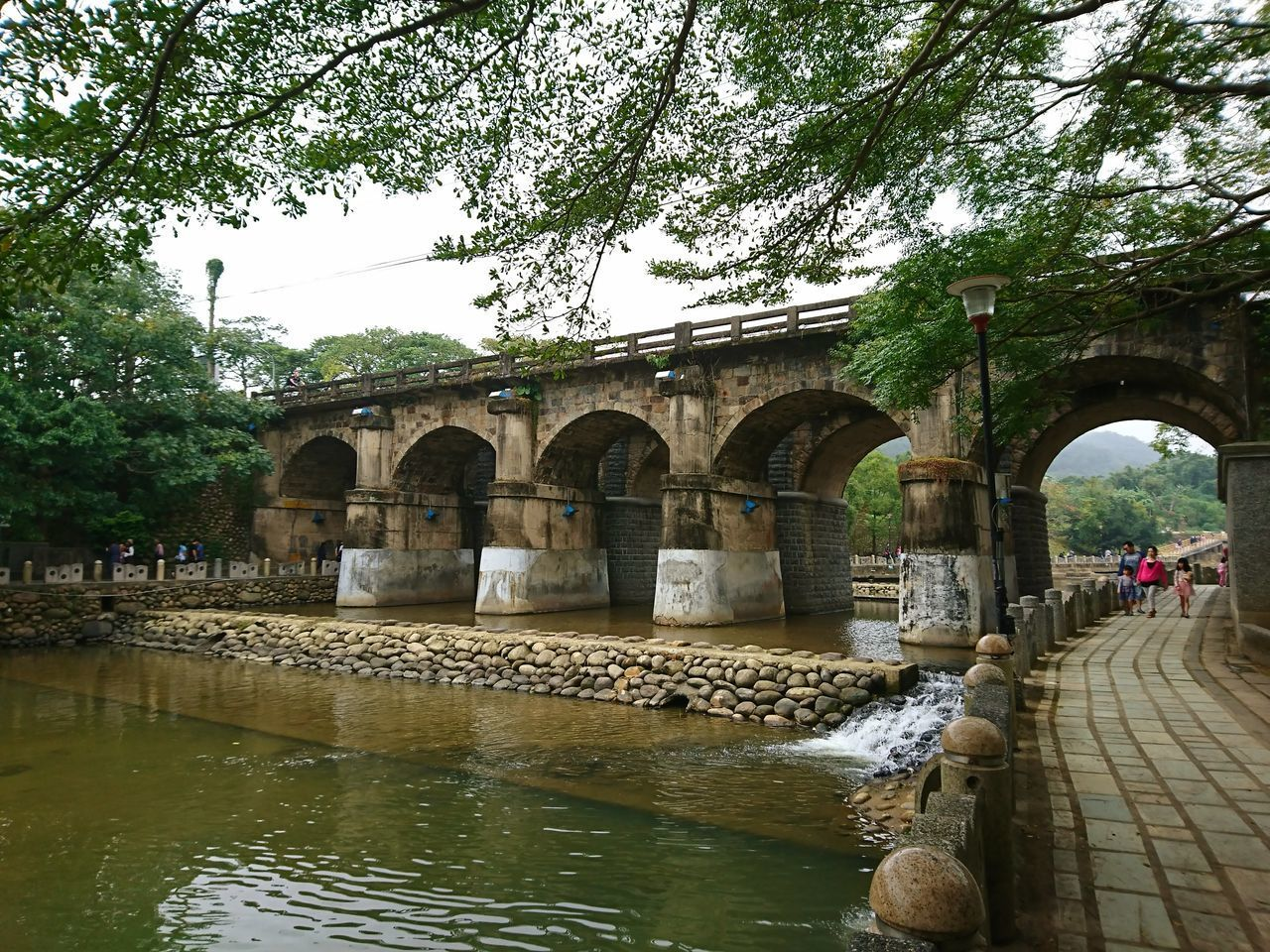 water, architecture, built structure, tree, arch, day, nature, plant, building exterior, connection, incidental people, waterfront, reflection, travel destinations, tourism, bridge, outdoors, history, architectural column, flowing water, arch bridge, flowing