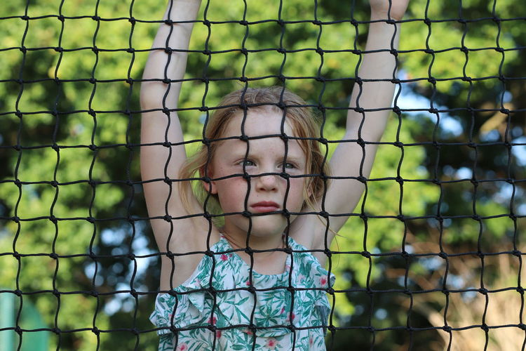 Portrait of girl seen through fence