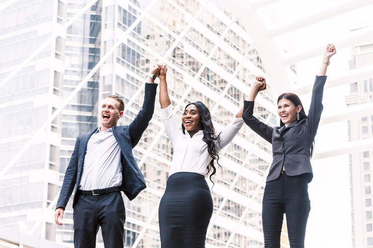 Group of businessmen in a row holding hands Adult Architecture Arms Outstretched Arms Raised Body Part Business Person Businesswoman City Coworker Emotion Excitement Front View Happiness Human Arm Human Limb Limb Smiling Three Quarter Length Well-dressed Women Young Adult Young Women