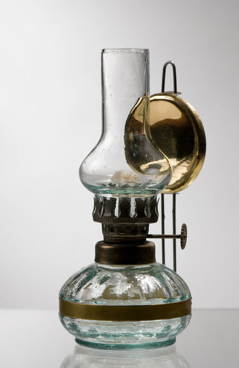 Single retro style glass decorative oil lamp or lantern standing on glass table surface and gray background, object in vertical orientation, nobody. Antique Decoration Decorative Glass Lamp Lantern Light Lighting No People Oil Old Paraffin Retro Unique Vintage Wick