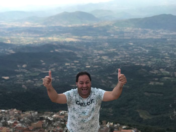 On The Top Gennargentu (Sardinia) Gennargentu National Park Gesturing Mountain Real People Arms Raised One Person Smiling Arms Outstretched Happiness Day Outdoors Lifestyles Looking At Camera Peace Sign - Gesture Nature Landscape Standing Men Cheerful Sky Portrait