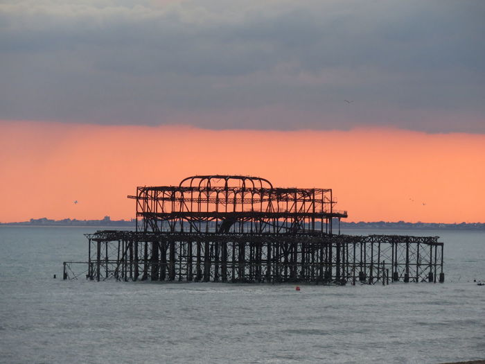 West Pier In Sea Against Sky During Sunset At Brighton
