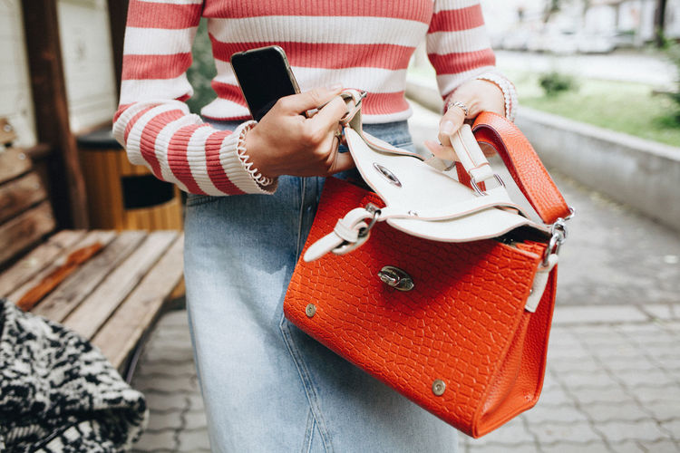 Midsection of woman holding bag