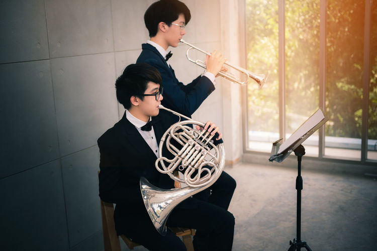 Portrait of couple teen musician playing instrument classic. Sitting Real People Holding Indoors  Young Adult Musical Instrument Lifestyles Casual Clothing Seat Men Two People Young Men Three Quarter Length People Boys Leisure Activity Adult Males  Young Women Playing