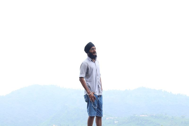 Young man wearing turban looking away against clear sky