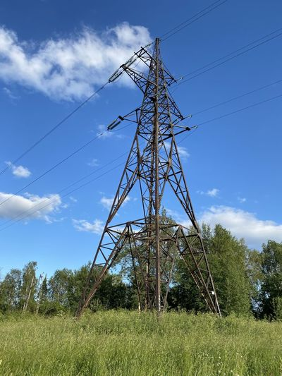 Low angle view of electricity pylon on field against sky