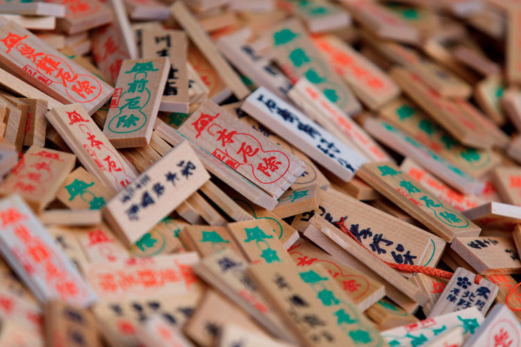 Ema - small wooden plaques, common to Japan, in which Shinto and Buddhist worshippers write prayers or wishes. Japan Wishes Religion Traditional Large Group Of Objects Full Frame Text Communication Letter Abundance No People Selective Focus Backgrounds Multi Colored Wood - Material Still Life Indoors  Western Script Alphabet High Angle View Close-up Choice Toy Variation