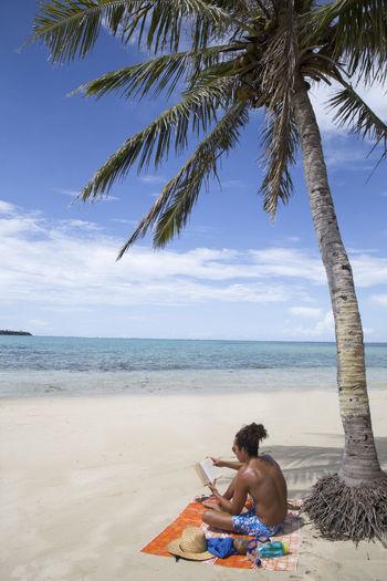 Full length of shirtless man sitting on beach