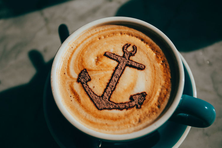 High angle view of anchor on froth art in coffee at table