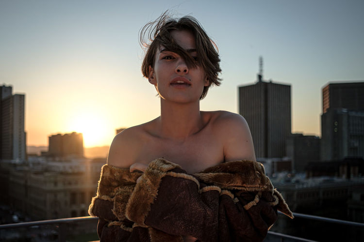 Portrait of young woman standing by railing in city against sky during sunset