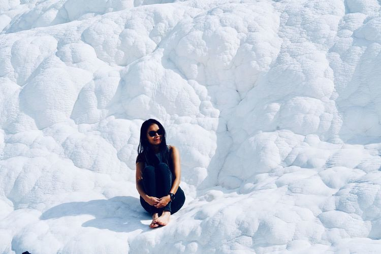 Full length of woman sitting on snow