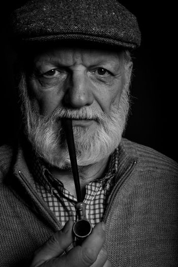 Portrait Of Senior Man With Smoking Pipe Against Black Background