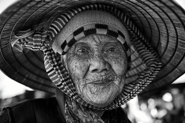 Close-Up Portrait Of Senior Woman Wearing Asian Style Conical Hat
