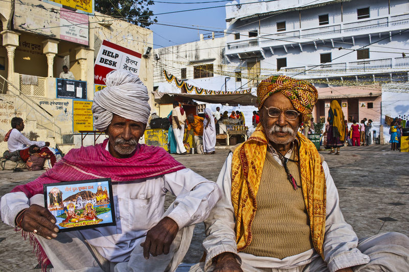 People sitting on street market in city