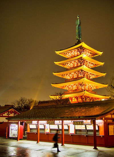 Illuminated traditional building against sky at night