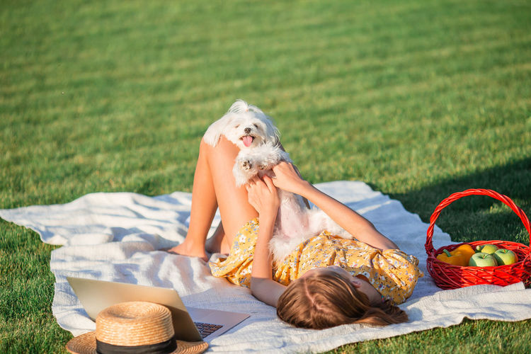 Girl lying on grass with dog at park