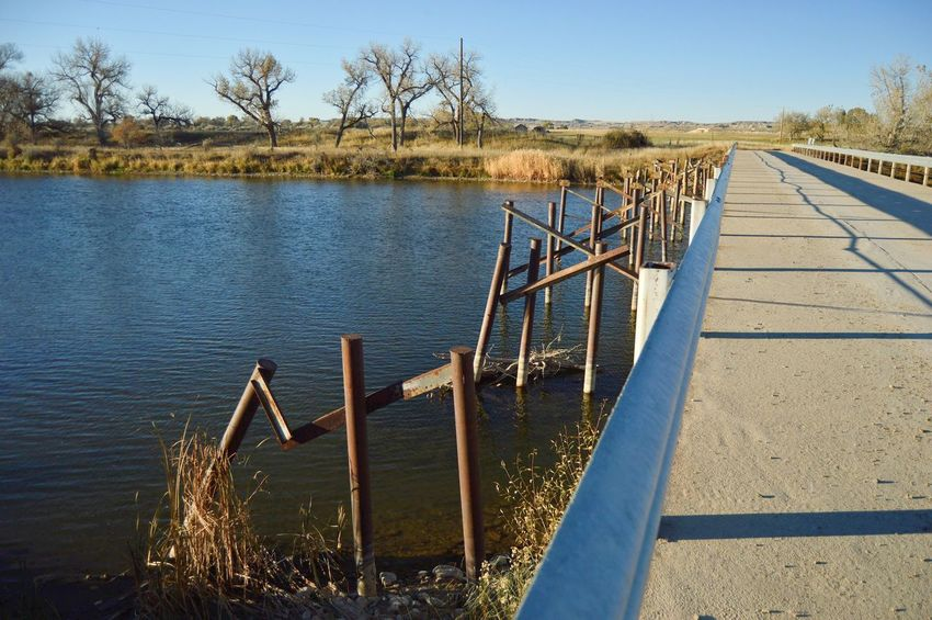 Old and new Clear Sky Facing North Rusted Late Evening Long Shadows Grass River South Of Orin Junction Wyoming Outdoors Shadows Water Tree Railing Sky