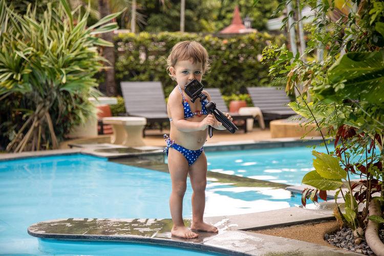 Full length of cute boy standing in swimming pool