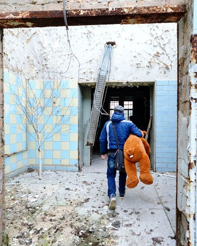 Rear view of man with toy walking towards abandoned house