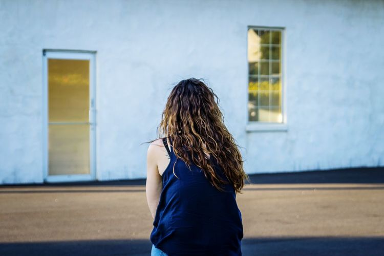 Rear View Of Woman Sitting Against Building